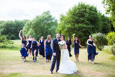 Photo of bridesmaids running toward bride and groom