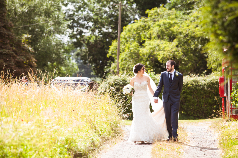 Photo of Bride & Groom walking along country lane in Oxford