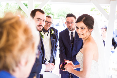 photo of best man presenting bride and groom with wedding rings