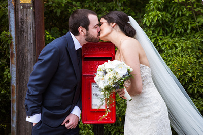 Photo of bride and groom kissing over red pillar box