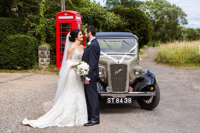 Photo of bride and groom by wedding car, Austin