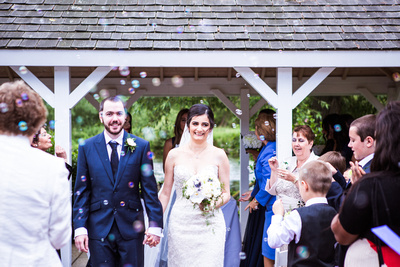 Photo of bride and groom leaving the ceremony, bubbles are being used instead of confetti