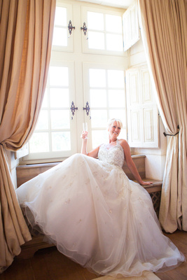 Bridal Portrait. Bride getting ready. She sits in the window of the chateaux drinking champagne