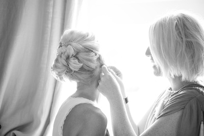 bridesmaid putting earrings on bride
