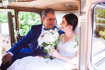Photo of bride and father of the bride in wedding car looking at each other