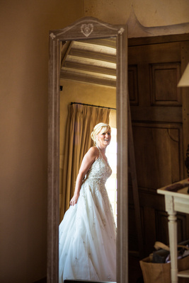 Bride in wedding dress looking in mirror, Chateaux wedding in France
