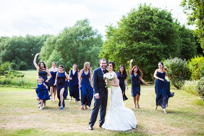 Photo of bridesmaids running toward bride and groom