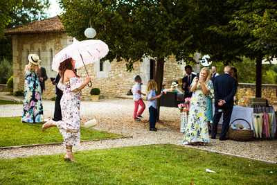 playing with parasols at wedding. Documentary style wedding photography