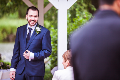 Photo of groom watching bride walk down aisle