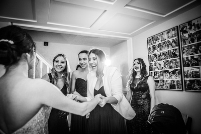 Photo of bridesmaids looking happy and delighted to see bride